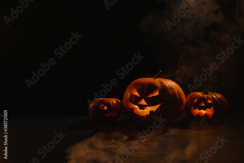 Photo Three creepy halloween steaming pumpkins with a carved luminous smirk on a black background