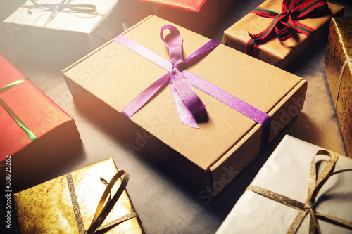 Fototapeta gift wrapping service - wrapped present boxes on dark table obraz