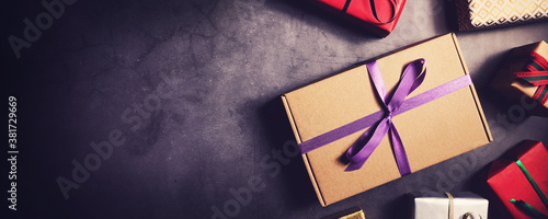 wrapped gift boxes on black stone background top view. banner copy space