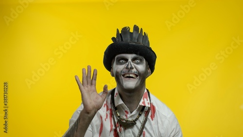 Fotografía Sinister man with professional Halloween skeleton makeup greeting someone, say h