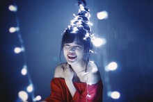 Christmas Portrait Of A Beautiful Smiling Girl With Christmas Tree Hairstyles And Lights