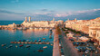 Beautiful panoramic aerial view photo from flying drone on Molfetta waterfront with the Old Cathedral San Corrado (Duomo Vecchio),port with ships and yachtsand the Molfetta city sunset. Apulia ,Italy