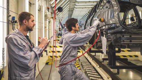Employees of the shop painting the car body check the quality Fototapet