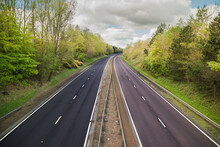 A Quiet Dual Carriage Motorway Devoid Of Traffic With Trees On Either Side And A Blue Sky Above