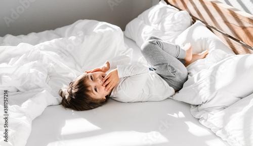 Fototapeta Cute little happy child boy playing in parents bed having fun at home at sunny morning