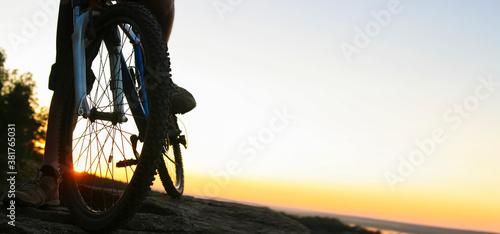 Silhouette of a bike. tourist on mountain peak. sunny dawn.