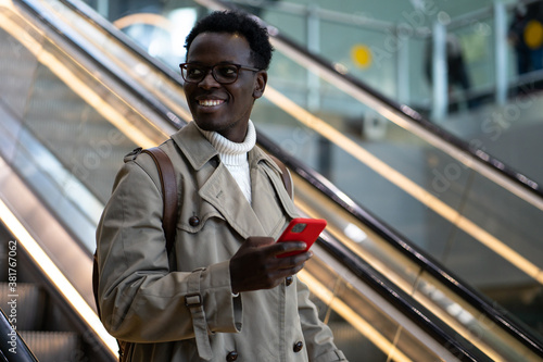 Smiling Afro-American traveler man stands on escalator in airport terminal or railway station, using mobile phone, looking aside, arrives from abroad Canvas