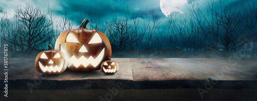 Jack O 'Lantern's with glowing eyes on a wooden table on spooky Halloween night Fototapet