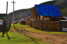 Road In Russian Village With Church And Houses With Blue Roof With Fence In The Evening At Sunset Light. Tractor, Pillars, Green Grass And Mountains Behind