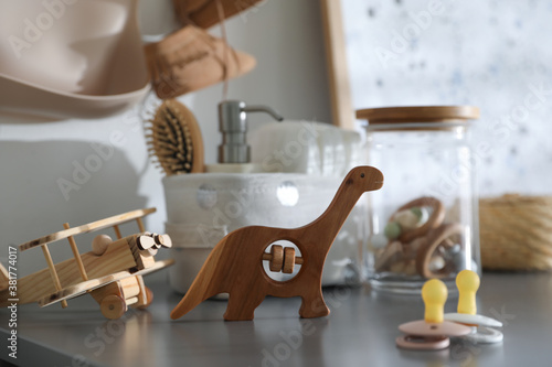 Fototapeta Wooden toys and pacifiers on grey table in child room obraz