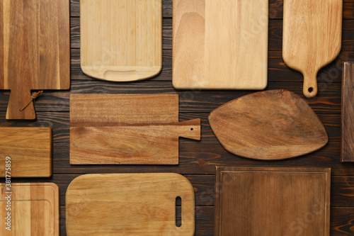 Fototapeta Set of wooden boards on brown table, flat lay. Cooking utensils