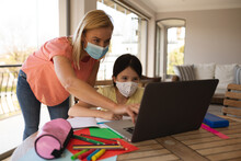 Mother And Daughter Wearing Face Masks Using Laptop At Home