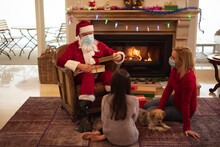 Santa Claus Wearing Face Mask Giving Gift Boxes To Young Girl