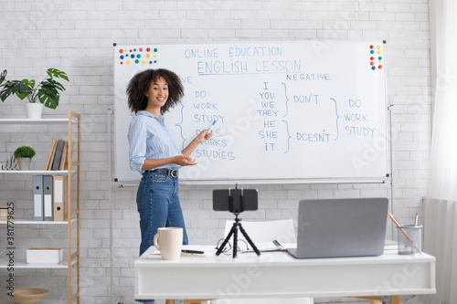 Smiling african american teacher points to white board with rules and records vi Tableau sur Toile