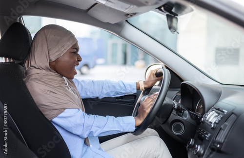 Leinwand Poster Angry Black Muslim Businesswoman Driving Car, Stuck In Traffic, Emotionally Beep