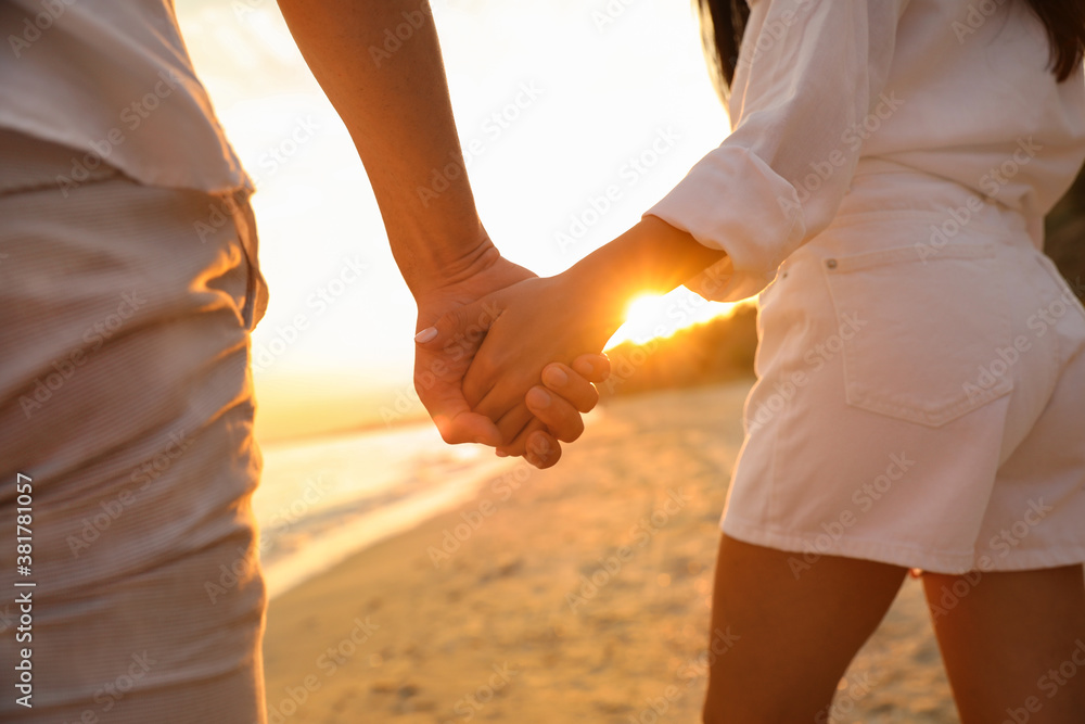 Fototapeta Lovely couple holding hands on beach at sunset, closeup