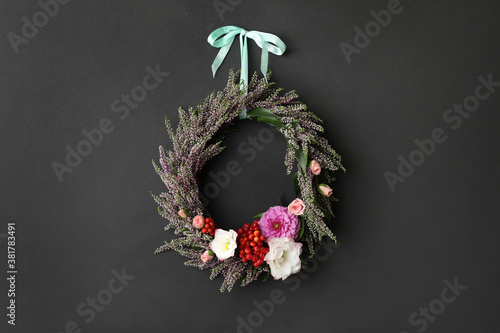 Beautiful autumnal wreath with heather flowers hanging on black background. Space for text