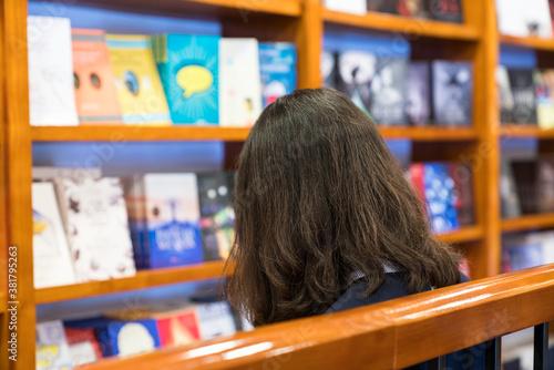 Vászonkép A girl reading book in the store closeup