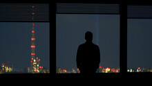 The Man Standing Near The Window On The Cityscape Background
