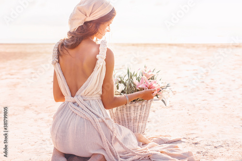 Fotografía beautiful young stylish woman with basket with flowers outdoors at sunset