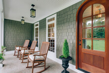 Arch Doorway Southern Covered Porch Wooden Rocking Chairs And Modern Light Fixtures With Green Bush