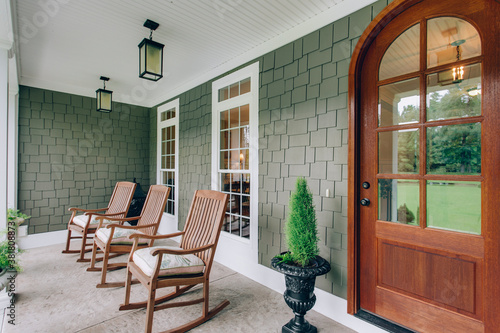 Fotomural Arch doorway southern covered porch wooden rocking chairs and modern light fixtu