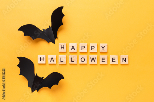 Halloween flat lay with text Happy Halloween and two flying bat on yellow backgr Wallpaper Mural