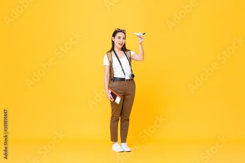 Cuadros en Lienzo Travel portrait of smiling young beautiful Asian tourist woman holding plane mod