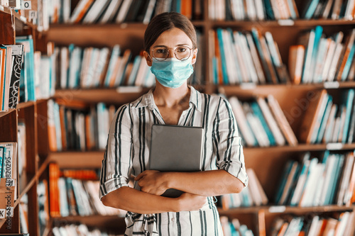 Fényképezés Beautiful intelligent freshman girl with face mask on standing in library and holding tablet in hands