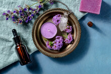 Aromatherapy Products, Shot From The Top With A Place For Text. Essential Oil, Scented Candle, Incense Cone And Aromatic Soap, Infused With Vervain And Lavender, On A Blue Background