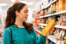Portrait Of A Young Caucasian Beautiful Woman Who Reads The Ingredients On The Product Packaging. Shelves With Goods In A Blur In The Background. The Concept Of Buying Goods And Shopping