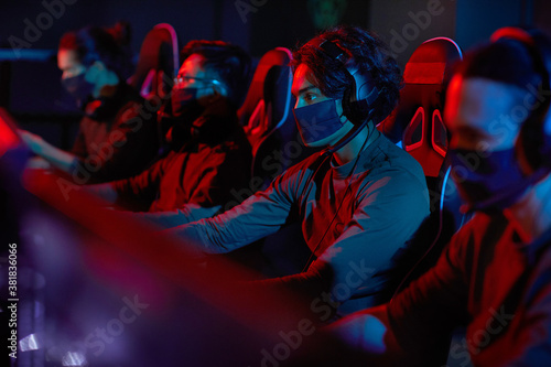 Photo Group of developers in protective masks sitting in front of computers and workin