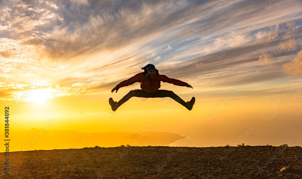 Fototapeta Happy man jumping for joy at sunset. Success, winner, happiness, ttavel concept.