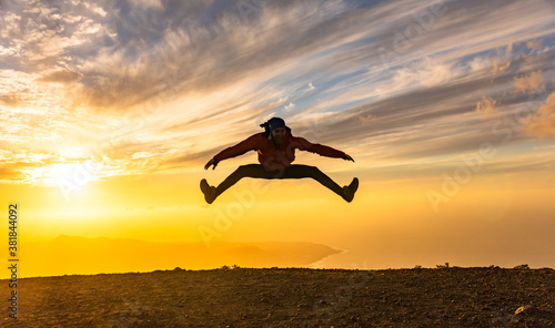Obraz Happy man jumping for joy at sunset. Success, winner, happiness, ttavel concept. - fototapety do salonu