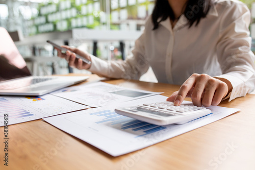 Fototapeta Close up businesswoman holding hand and calculator and using mobile phone and laptop computer on office desk,Business communication concept obraz
