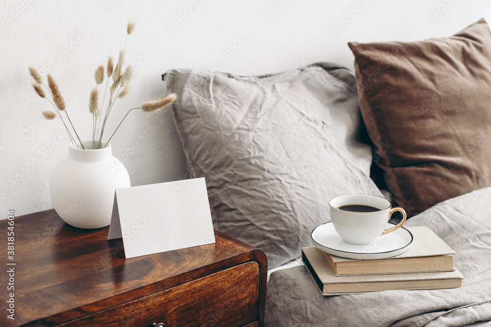 Fototapeta Empty greeting, place card mockup on retro wooden bedside table. Modern white ceramic vase with dry Lagurus ovatus grass and cup of coffee. Beige linen and velvet pillows. Scandinavian bedroom