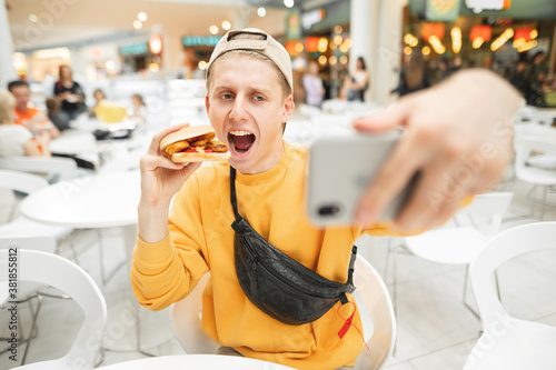 Photo Happy young man sitting at fast food restaurant eating burger and taking selfie