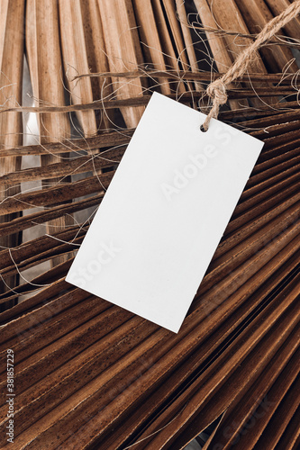 Closeup of blank gift, product tag mock-up with natural rope on dry palm leaves. Empty paper label. Tropical still life composition. Branding, summer sale concept. Flat lay, top view., vertical