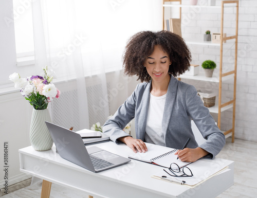 Adopt an order from clients in online office at home during outbreak. Cheerful african american female manager works at table with laptop and writes in notebook
