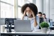 Overwork, illness and disease symptoms in workers. African american woman in protective mask suffers from headache, sitting at table with antiseptic, laptop in office interior