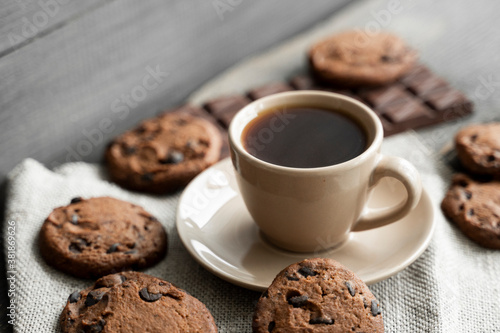 Coffee cup with cookies and chocolate on wooden table background. Mug of black coffee with chocolate cookies. Fresh coffee beans.