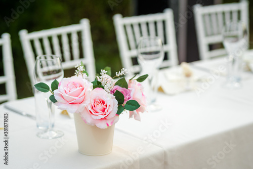 Wedding table decoration. Outdoor table decoration with an artificial flower pot.