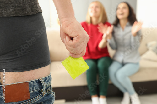 Fotomural Man stands in shorts with his pants down and holds condom in front of two women
