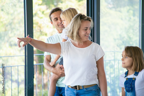 Beautiful mother pointing somewhere and cute daughter looking at that Fototapeta