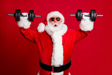 Photo Of Pensioner Old Man White Beard Lift Dumbbells Shocked Easily Lifting Heavy Weigth Prepare Before Competition Wear Santa Costume Sunglass Headwear Isolated Red Color Background