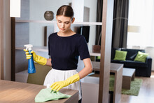 Chambermaid In Apron And Rubber Gloves Holding Spray Bottle And Rag While Cleaning Wooden Surface In Hotel Room