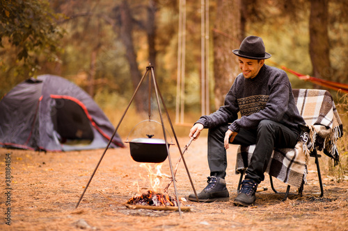 Young man camping in tent on autumn and cook food on campfire Fototapet