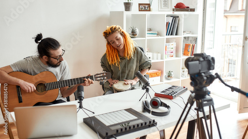Music is art. Man playing guitar and woman playing rhythm with djembe drum while recording video blog or vlog. Couple of musicians making music at home.