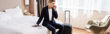 Panoramic Shot Of Businesswoman In Suit Talking On Smartphone While Sitting On Bed Near Luggage In Hotel