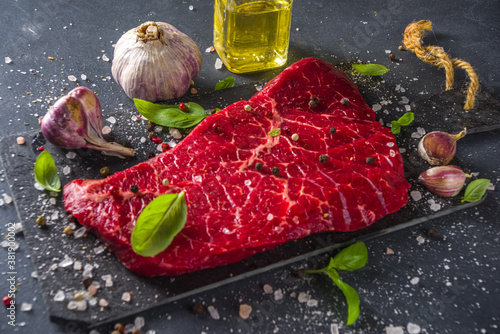 Cuadros en Lienzo Raw meat beef steak on black background, with herbs and spices, top view